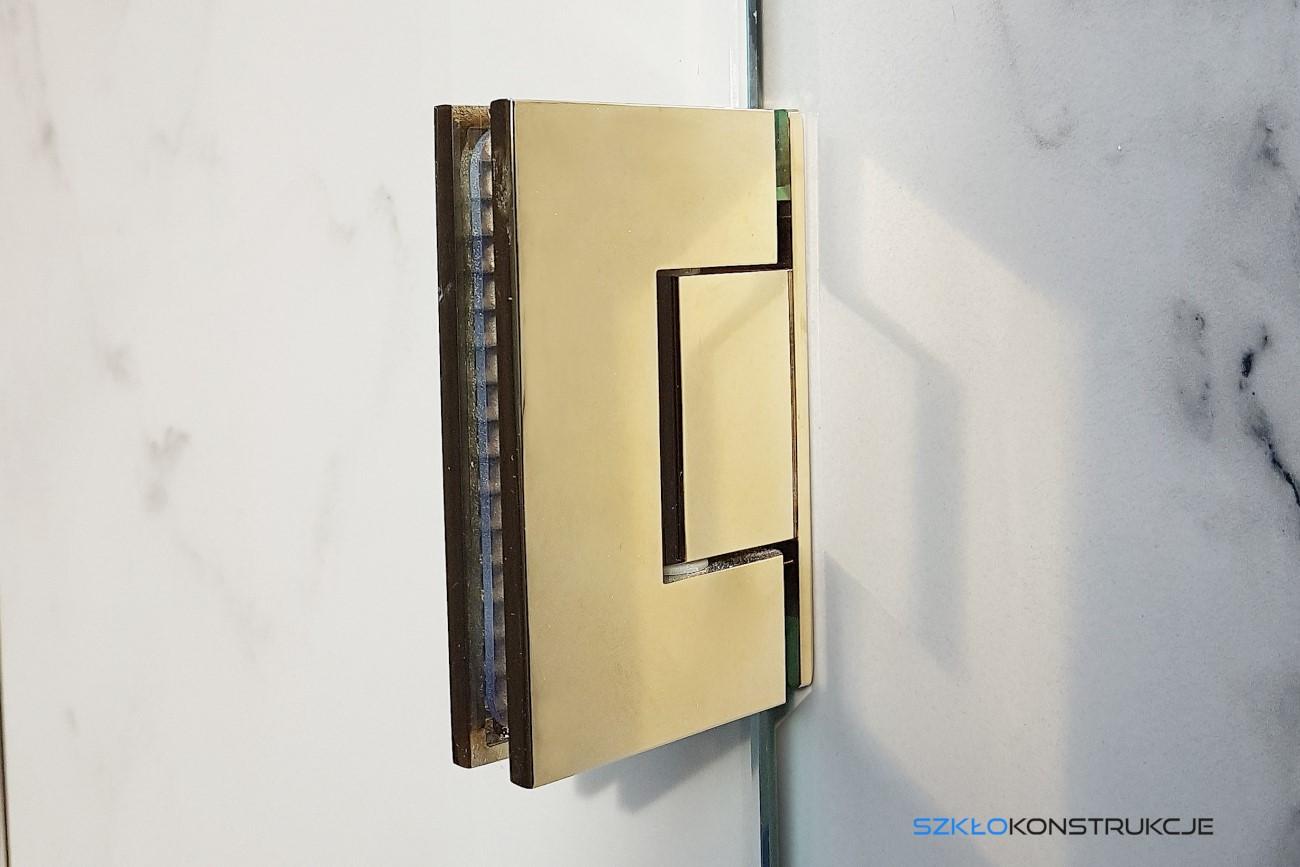 złoty zawias na szklanych drzwiach kabiny prysznicowej