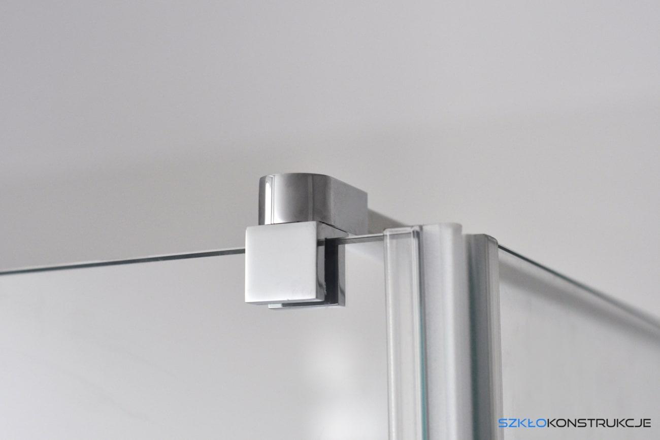 Stalowy uchwyt w kabinie prysznicowej.